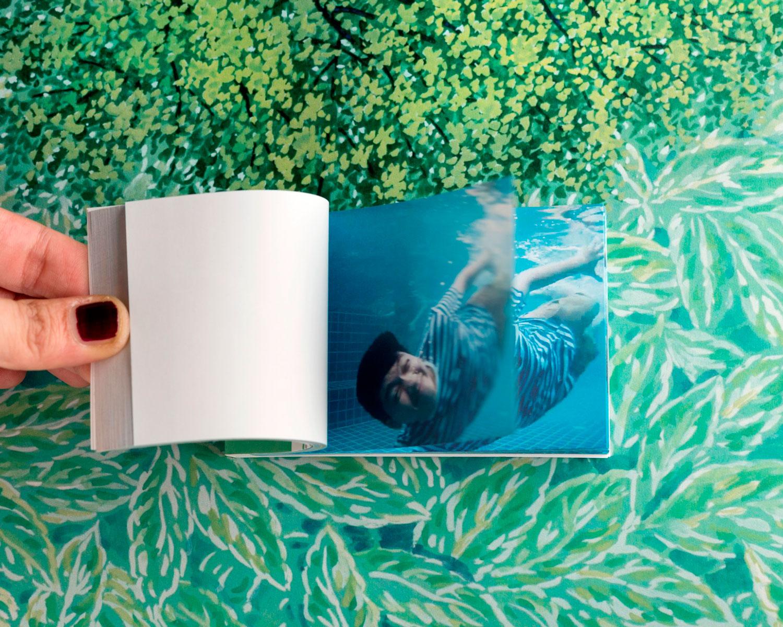 Ragazzo nuota in piscina e fa delle smorfie. Il flipbook è un modo originale di ricordare un breve momento. Stampiamo video con la tua storia
